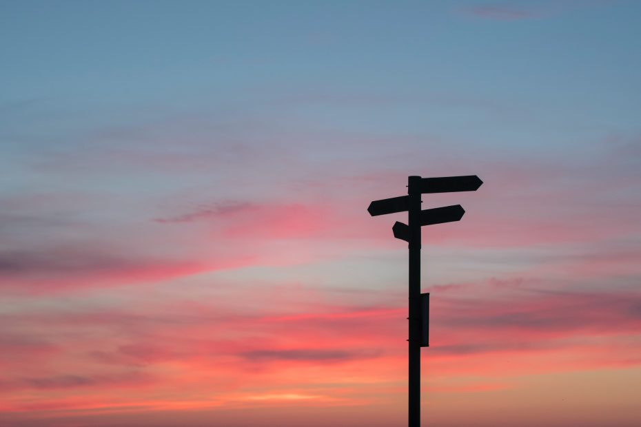 direction pole in the sunset